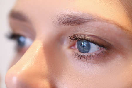 Close-up of female face with natural makeup. Lovely black eyelashes covered with mascara