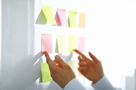 Close-up of worker hand holding colorful papers for notes with information