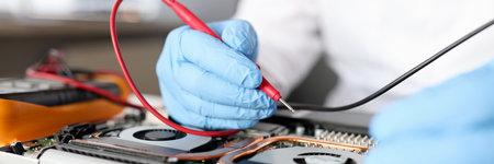 Gloved handyman repairs motherboard. Maintenance and repair of computer equipment