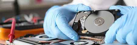 Gloved master holds a hard drive closeup
