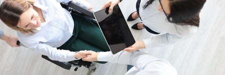 Businesswoman in wheelchair shakes hands with businessman next to awoman with tablet
