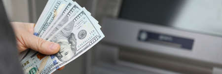 A man withdraws cash on the street at an ATM