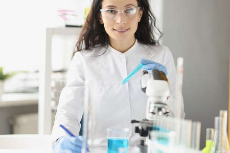 Woman chemist holds in hand a glass for test tube, with liquid solution of blue color