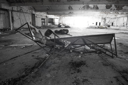 Black and white wide angle shot in a disused warehouse of a smashed table photo
