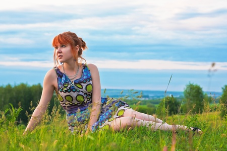 Beautiful ginger-haired woman in sundress sitting on the ground photo