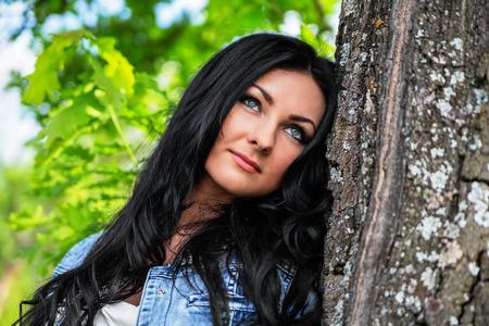 face in tree bark: Portrait of beautiful brunette woman near a tree Stock Photo