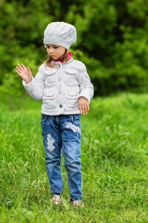 flapping: Young girl standing on a green lawn and flapping mosquitoes away Stock Photo