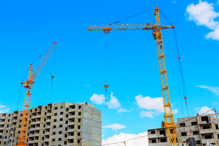 Cranes on the construction site on a background of blue sky 版權商用圖片