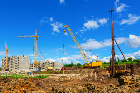 overhang: Cranes on the construction site beneath blue cloudy sky