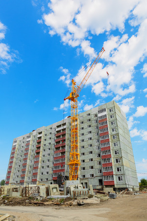 concrete construction: Dwelling house and tower crane on the construction site beneath blue cloudy sky