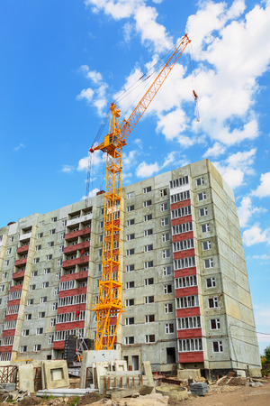 overhang: Dwelling house and tower crane on the construction site beneath blue cloudy sky