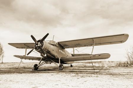 Old airplane on field in sepia tone Standard-Bild
