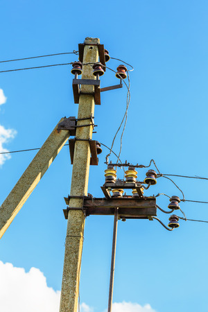 wattage: Electrical post with power line cables against blue sky