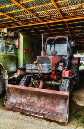 motor de carro: Tractor viejo bajo cobertizo en el patio trasero