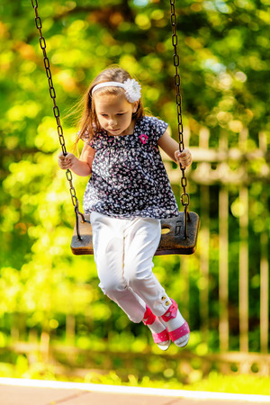 teeter: Pretty little girl swinging on seesaw in summertime Stock Photo