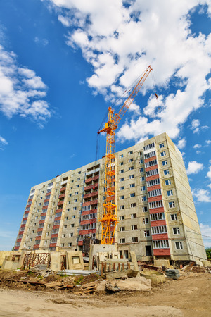 dwelling: Dwelling house and tower crane on the construction site beneath blue cloudy sky