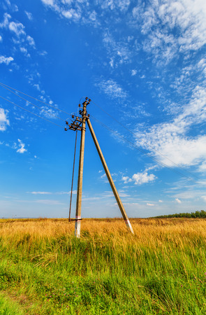 powerline: Powerline beneth blue sky with cumulus clouds Stock Photo