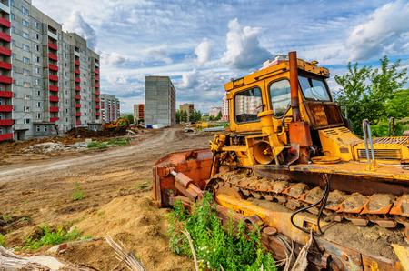 motor de carro: Vista de la obra de construcci�n (excavadora y casas bajo el cielo nublado) Foto de archivo