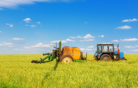 spattering: Farming tractor spraying green field beneath blue sky with white clouds