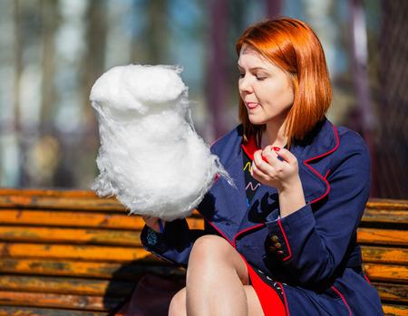 algodon de azucar: Joven y bella mujer comiendo algodón de azúcar en el parque