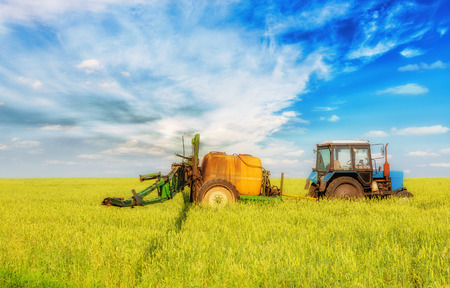 agronomic: Farming tractor spraying green field beneath blue sky with white clouds