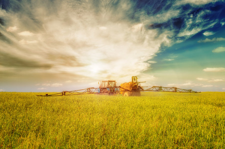 spattering: Farming tractor spraying green field beneath blue sky with white clouds and shining