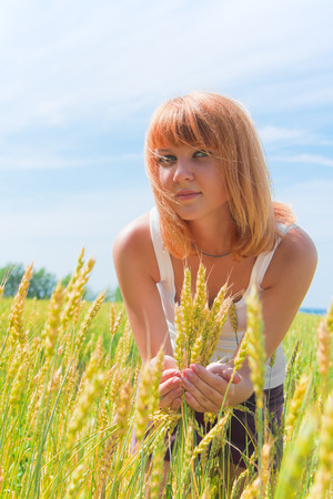 wheatfield: Beautiful young red-haired woman at wheatfield in summer day Stock Photo