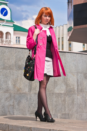 reticule: Beautiful ginger-haired woman in pink coat with reticule Stock Photo