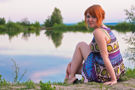 woman resting: Beautiful ginger-haired woman in sundress sitting at the coast of pond
