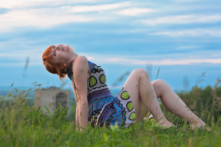 sitting on the ground: Beautiful ginger-haired woman in sundress sitting on the ground