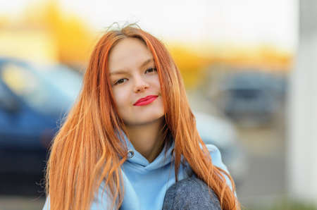Smiling teen girl in hoodie looking at camera. Shallow dof