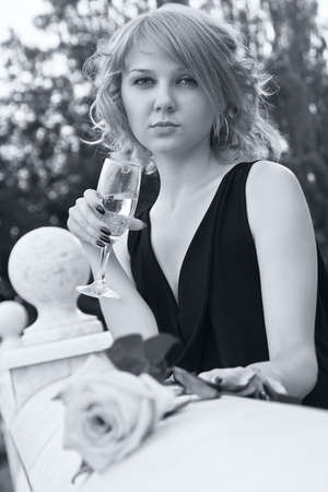 Beautiful woman drinking champagne from wineglass in black and white with soft blue tint 版權商用圖片