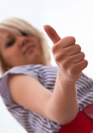 Beautiful young woman showing thumb's up sign
