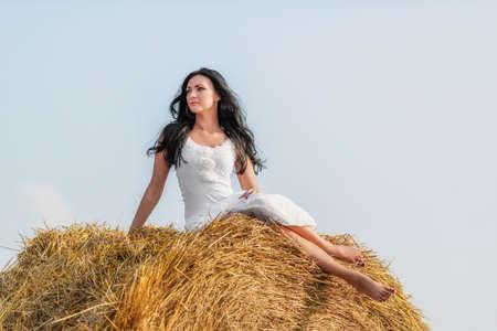 Beautiful brunette woman sitting on hay bale in warm summer day