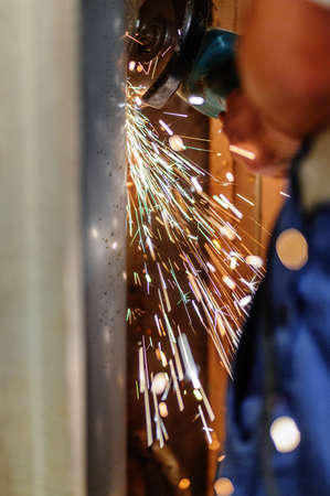 Grinding metal pipe with a grinder and throwing off bright sparks around