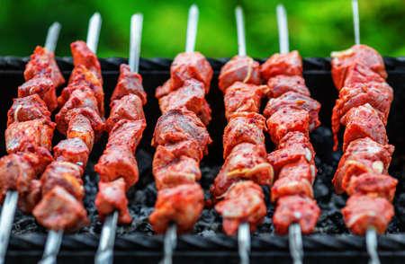 Pork shashlik being roasted on skewers over charcoal