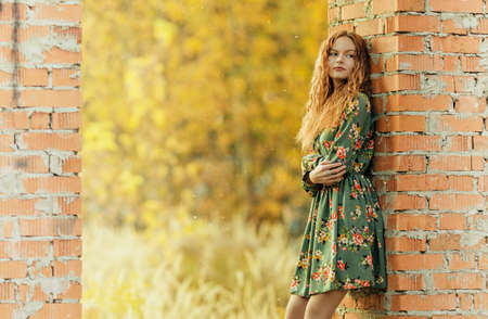 Teen girl in dress standing near a brickwork in abandoned place. Shallow dof