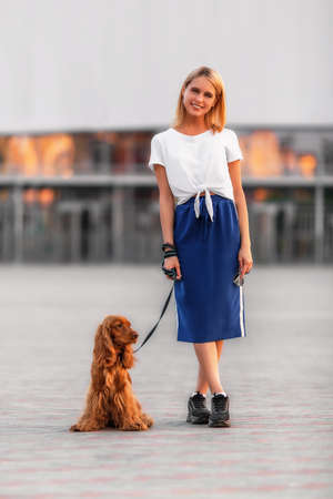 Portrait of a young attractive woman smiling at camera with spaniel dog. Shallow dof