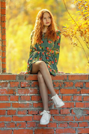Teen girl in dress sitting on brickwork in abandoned place. Shallow dof 版權商用圖片