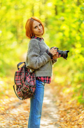 Woman photographer in autumn forest. Shallow dof