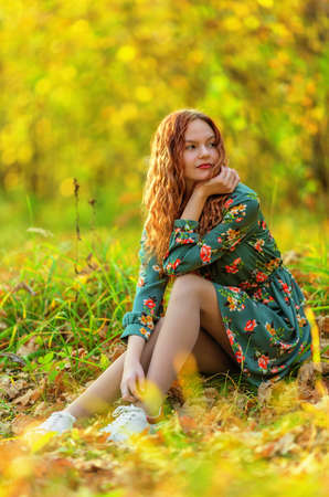 Teen girl in dress sitting on the ground in autumn forest. Shallow dof
