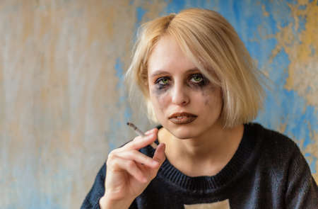 Portrait of sad woman with cigarette and makeup running down sitting at wall