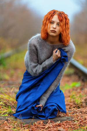 Woman in sweater and blue dress sitting on railway path in autumn day. Shallow dof