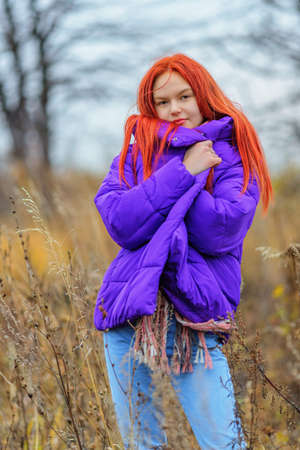Smiling ginger-haired teen girl covering up in violet jacket in autumn day. Shallow dof 版權商用圖片