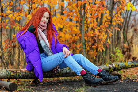Smiling ginger-haired teen girl in violet jacket sitting on log in autumn day 版權商用圖片