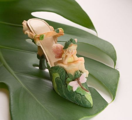 Thumbelina-shoe on a white background on a green leaf (miniatures) Series photo