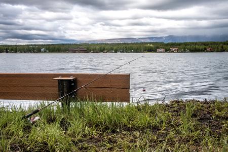 曇りの日に湖の横にあるベンチに寄りかかってポールを釣り 写真素材