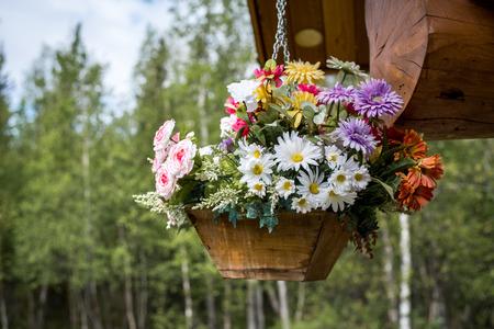 log basket: lower basket full of flowers hanging from front porch of log cabin, horizontal