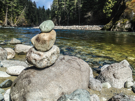 Piled rocks form a cairn next to a river with woods in the background