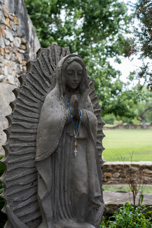 statue of virgin mary with rosary beads in a prayer garden